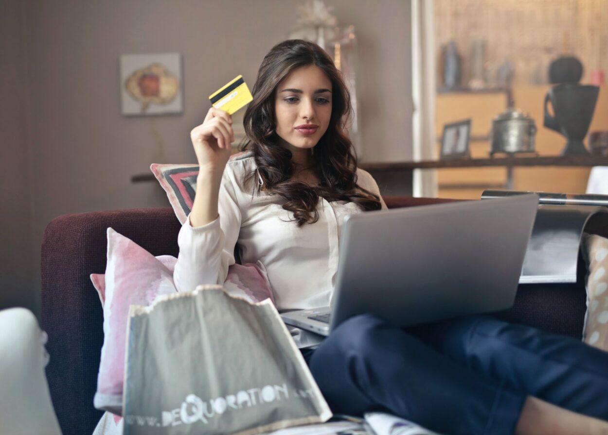 Kobieta z karta kredytową siedzi przed komputerem - zakupoholizm